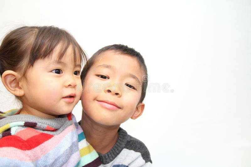 Japanese brother and sister hugging each other. 7 years old boy and 2 years old girl stock photo