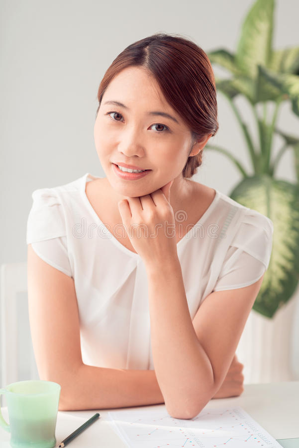 Japanese business lady. Pretty Japanese business lady working with financial report royalty free stock photography