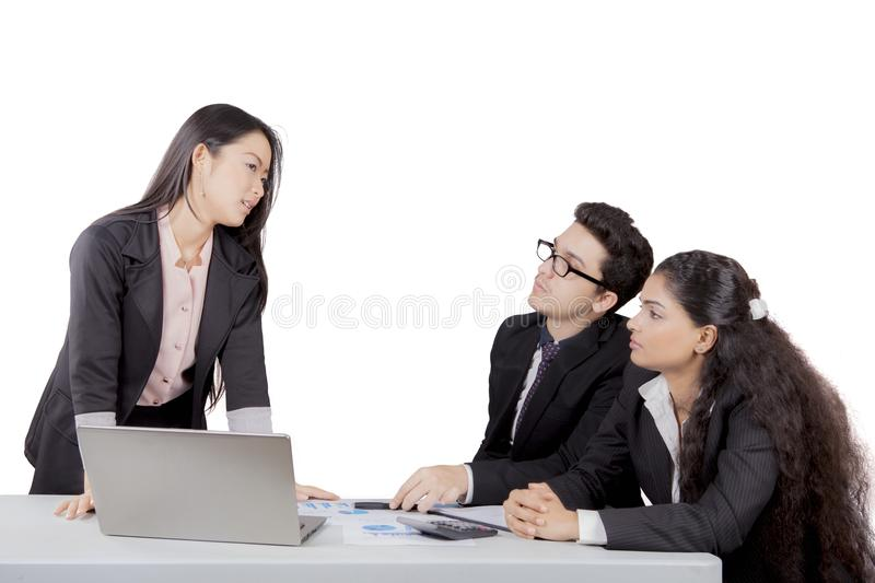 Japanese business manager talks to her staff. Isolated over white background royalty free stock image