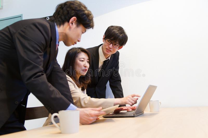 Japanese business person checking internet web site with PC. Three person, Japanese men, Japanese woman, business documents, laptop computer, internet content stock photos