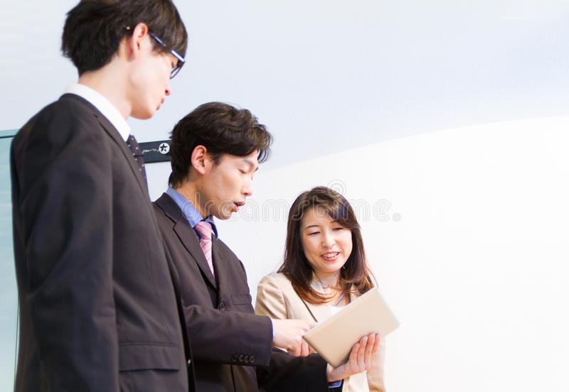 Japanese business woman and business men talking at desk, looking at documents on tablet device. Japanese men and woman, talking at team meeting, in front of stock image