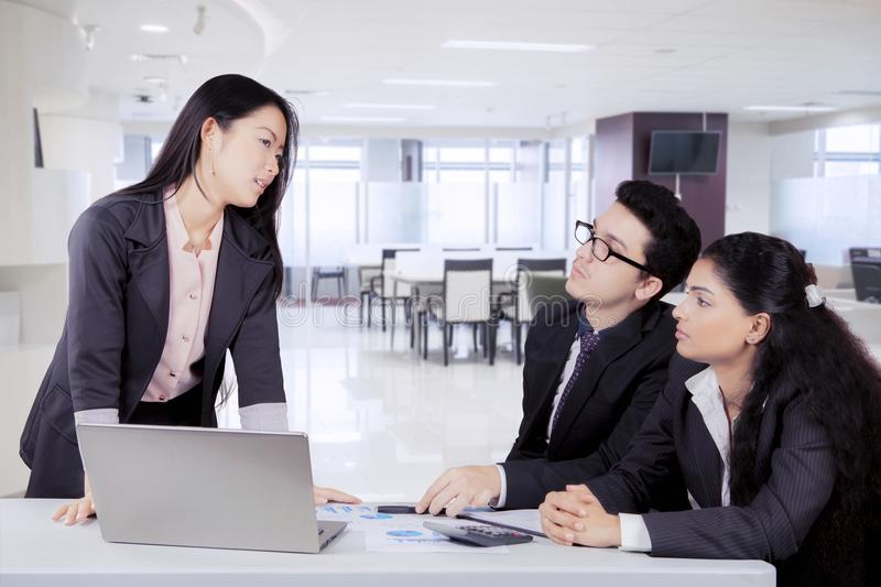 Japanese business woman talking to her colleagues. Japanese business women talking to her colleagues in a meeting stock photography