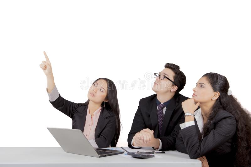 Japanese businesswoman pointing to blank space while other team members pay attention stock photo