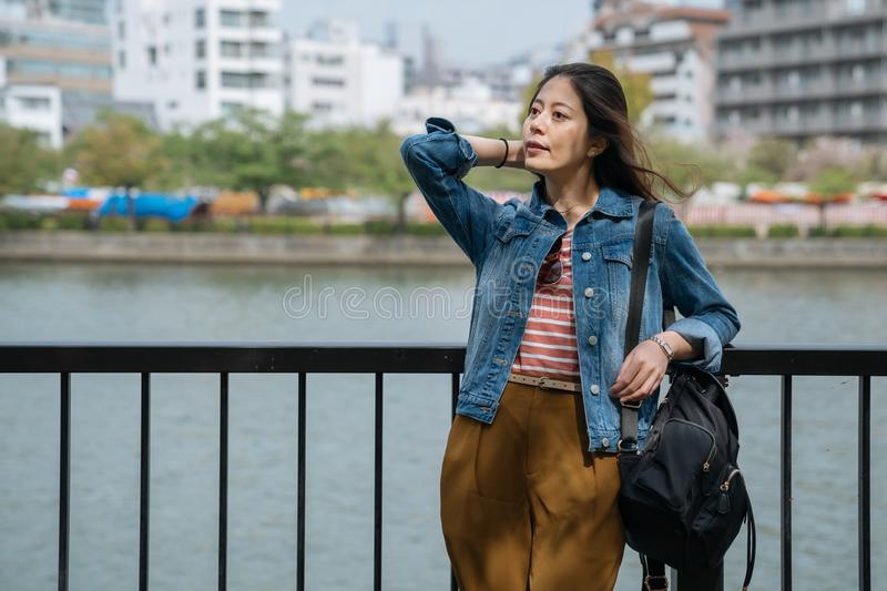 Japanese businesswoman relaxing near the clean river with winds blowing hair on holiday. young office lady rest relying on stock image