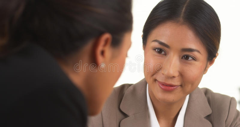 Japanese businesswoman talking with Mexican colleague royalty free stock photo