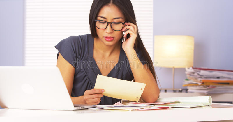 Japanese businesswoman talking on smartphone while doing paperwork stock photo