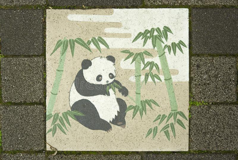 Japanese ceramic tile decorated with cute panda eating bamboo le. Aves in the Koishikawa Korakuen Park street stock image