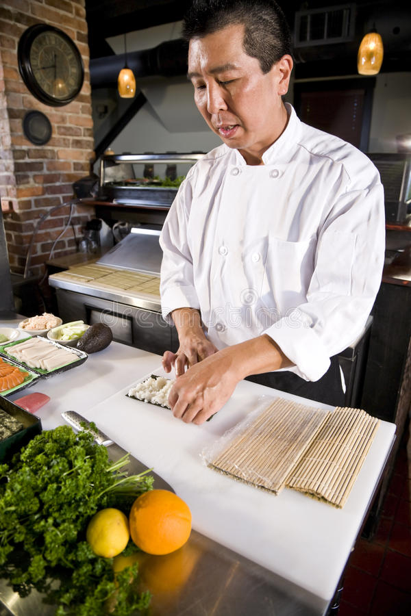 Japanese chef in restaurant making sushi roll stock photo