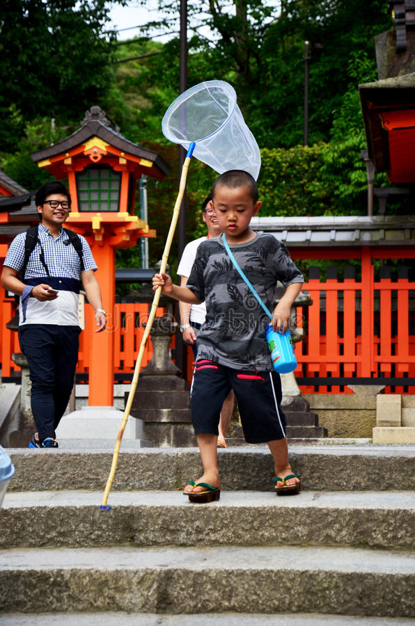 Japanese children people holding Insect net or Swing fishing net. S and running go to garden Fushimi-Inari Shrine on July 11, 2015 in Kyoto, Japan royalty free stock image