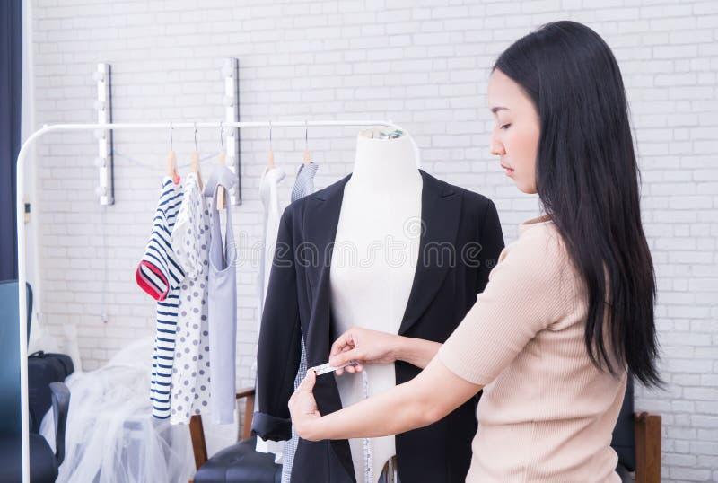 Japanese fashion designer is measuring jacket royalty free stock photos
