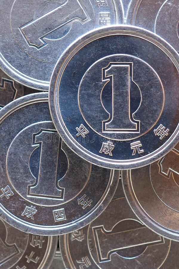 Japanese coins at 1 yen close-up. The surface of many of these coins. Information and news about the economy, finance, banks of. Japan. Vertical shot. Macro royalty free stock photography
