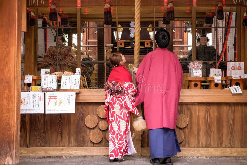 Japanese couple dressed in traditional costume prays for luck and blessing in old temple royalty free stock photos