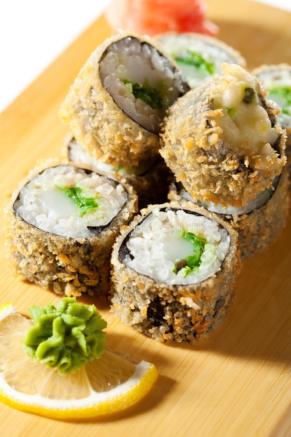 Japanese Cuisine - Deep-fried Sushi Roll. With Scallop and Chuka Seaweed inside. Served on Wooden Plate stock image