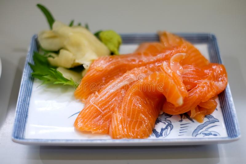 Japanese cuisine, Fresh Salmon sashimi on  plate. Japanese cuisine, Fresh Salmon sashimi and sushi roll with green salad on white plate isolated on white royalty free stock image