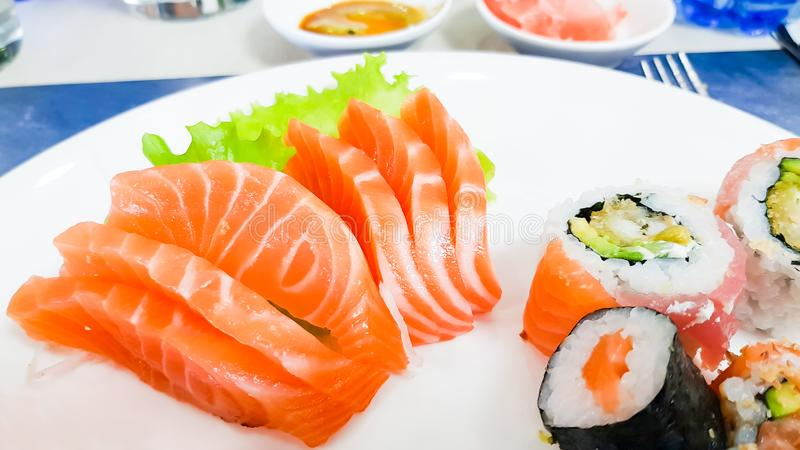 Japanese cuisine, Fresh Salmon sashimi and sushi roll with green salad on white plate  on white background.  royalty free stock photos