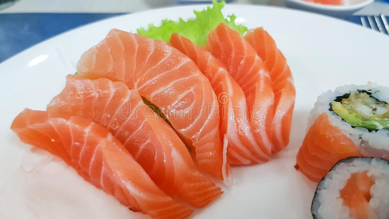 Japanese cuisine, Fresh Salmon sashimi and sushi roll with green salad on white plate  on white background.  stock photo