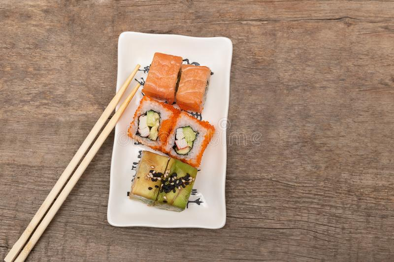 Japanese cuisine. Sushi rolls on white plate, wooden background.  stock photography