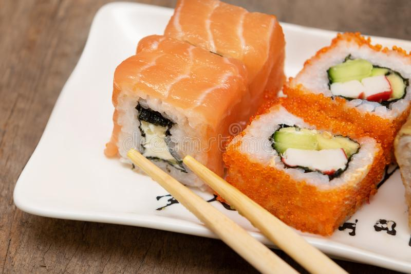 Japanese cuisine. Sushi rolls on white plate, wooden background.  royalty free stock images