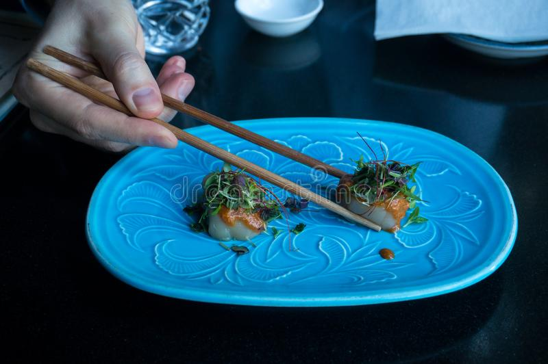 Japanese cuisine raw scallop dish served with herbs and sauce. Eating raw scallop dish served with herbs and sauce with chopsticks. Japanese cuisine restaurant stock photography