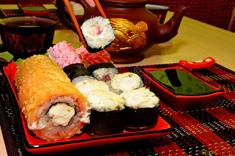 Japanese cuisine, rolls and sushi. Lunch in Japanese,eat with chopsticks,tea ceremony,Japanese cuisine, rolls and sushi,red sushi dishes, clay teapot and mugs stock image