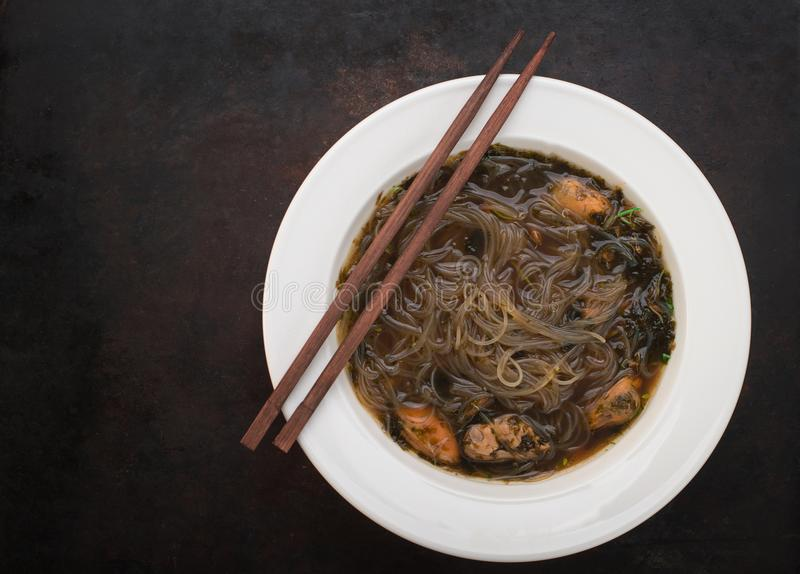 Japanese cuisine, soup with chashu pork, chives, sprouts, noodles and seaweed on the table under the sunlight. Old black rustic ba royalty free stock photography