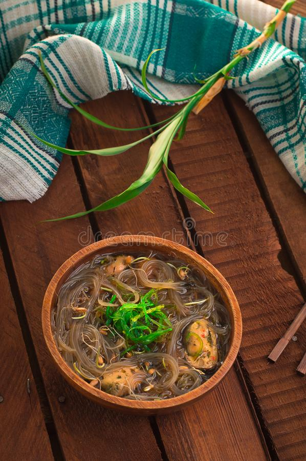 Japanese cuisine, soup with chashu pork, chives, sprouts, noodles and seaweed on the table under the sunlight. Wooden rustic backg royalty free stock images