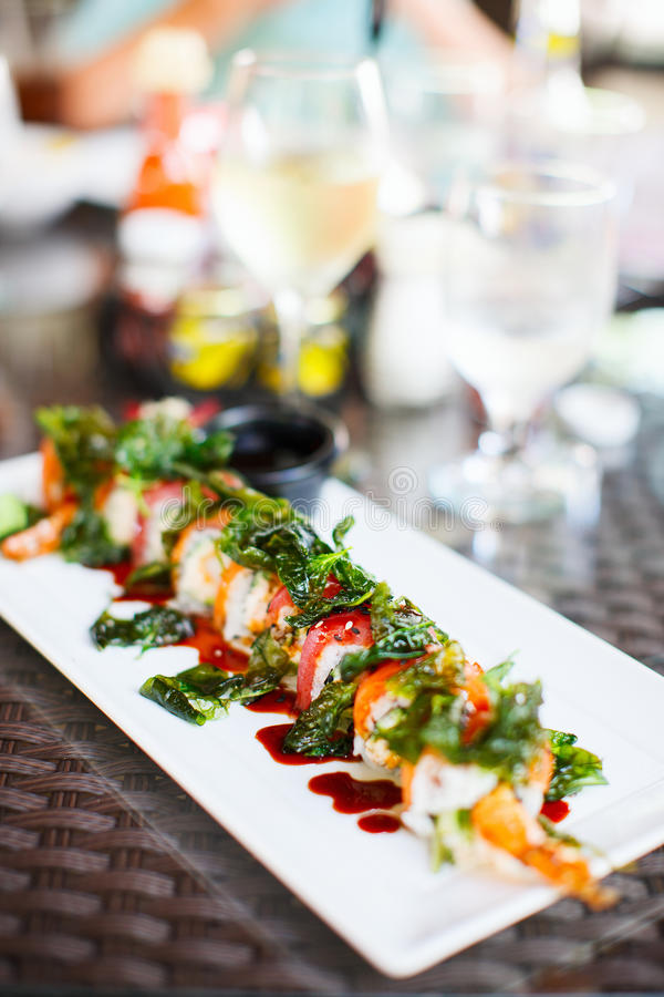 Japanese cuisine sushi rolls. Japanese cuisine delicious sushi rolls with salmon, crab meat and shrimp topped with spinach leaves at restaurant stock photography