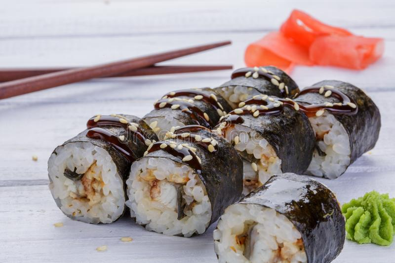 Japanese Cuisine - Sushi and Rolls with Seafood, Vegetables, Cream Cheese on a white wood background. Rolls, ginger, wasabi stock photos