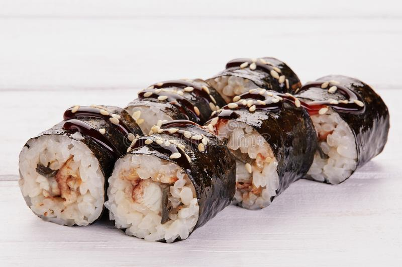 Japanese Cuisine - Sushi and Rolls with Seafood, Vegetables, Cream Cheese on a white wood background. royalty free stock image