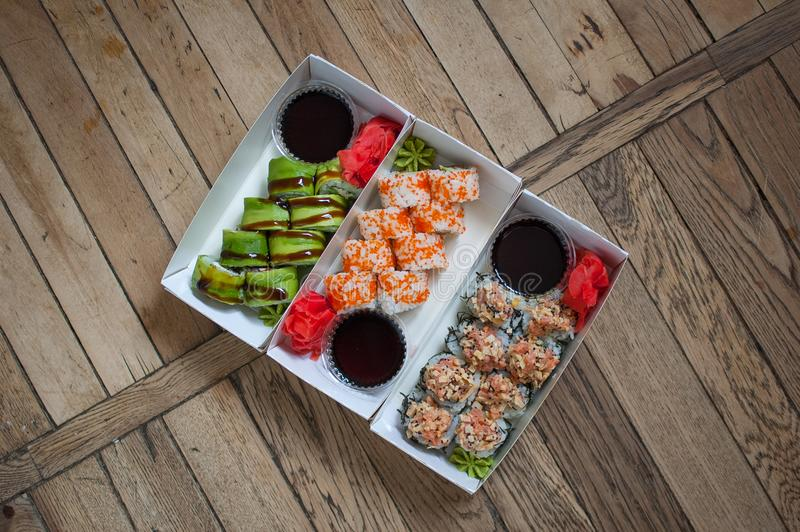 Japanese cuisine. Sushi set on a tree carton box over wooden background. Food for take away or sushi delivery concept.  royalty free stock photos