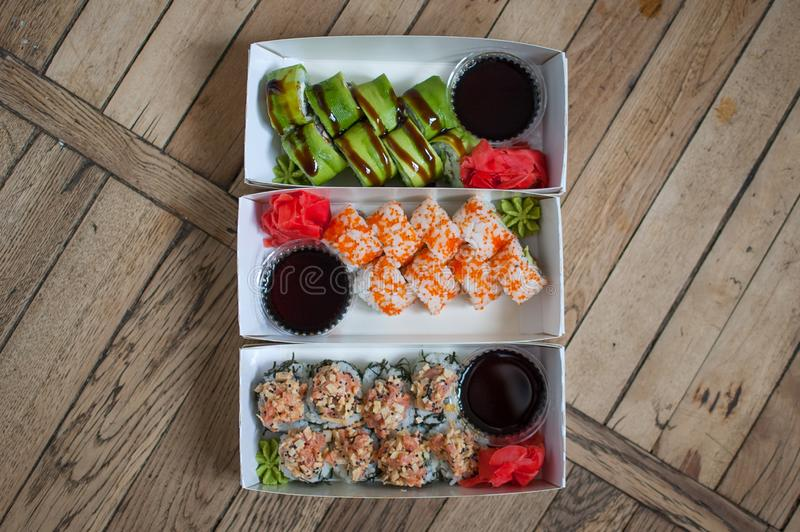 Japanese cuisine. Top view of sushi set on a carton box over wooden background. Food for take away or sushi delivery. Concept royalty free stock photo