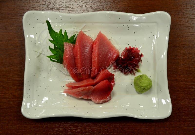Japanese cuisine, Tuna sashimi. On white square ceramic dish royalty free stock photo