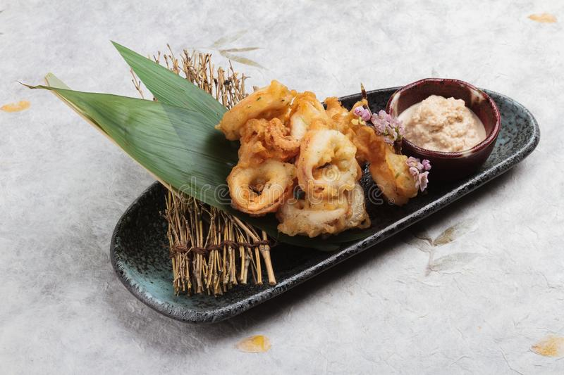 Japanese deep fried squid mixing tempura flour Squid Karaage served with sauce in black plate washi Japanese paper royalty free stock images