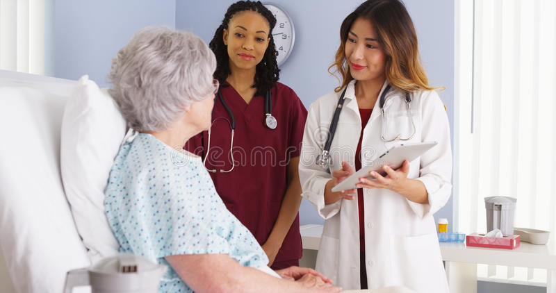 Japanese doctor and black nurse talking to elderly woman patient in hospital bed royalty free stock images
