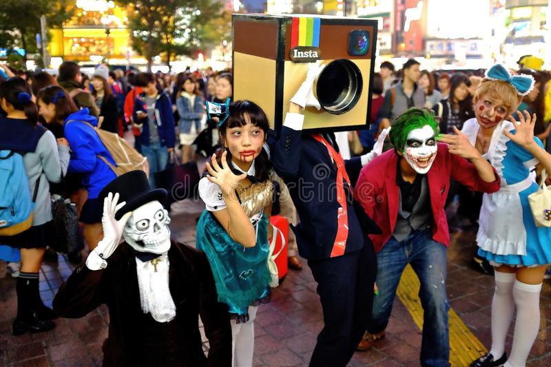 Japanese dressed in Halloween costumes pose for a group picture at Shibuya Hackiko Square in 2014. royalty free stock image