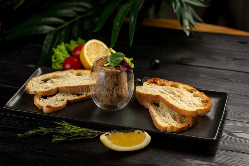 Japanese duck pate with warm ciabatta on a black plate on a black wooden background stock photography