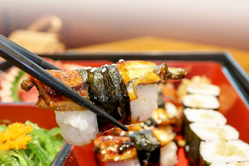 Japanese eel or Unagi Sushi Rolls in the chopsticks wooden table background, at the japanese restaurant. Japanese Foods Concept. stock image