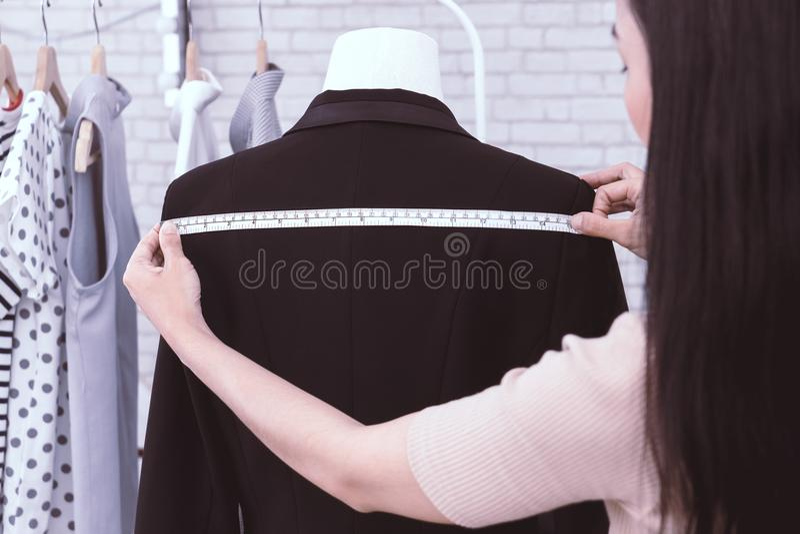 Japanese fashion designer measuring jacket shoulder stock photo