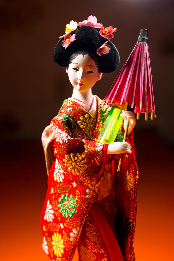 Japanese female kimono doll wearing red paper umbrella with flowers in hair and green glowing tritium trinket royalty free stock images