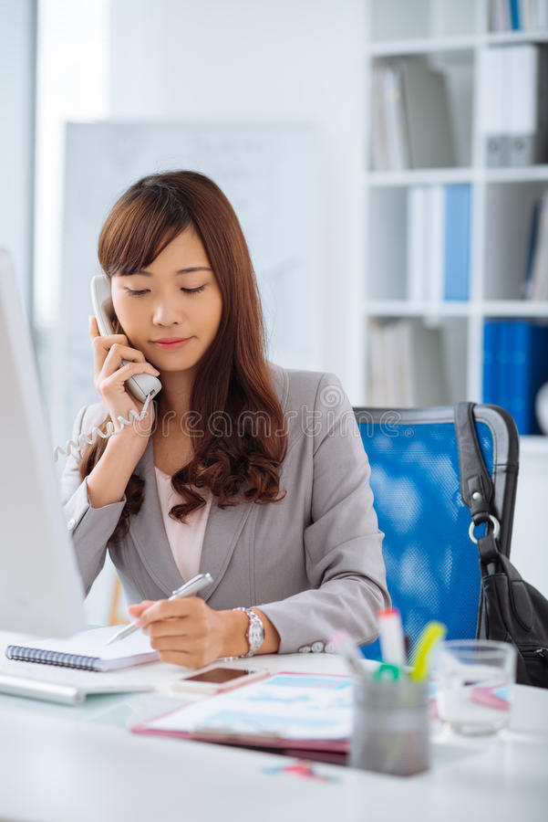 Japanese female manager. Pretty Japanese manager talking on the phone and making notes stock photography