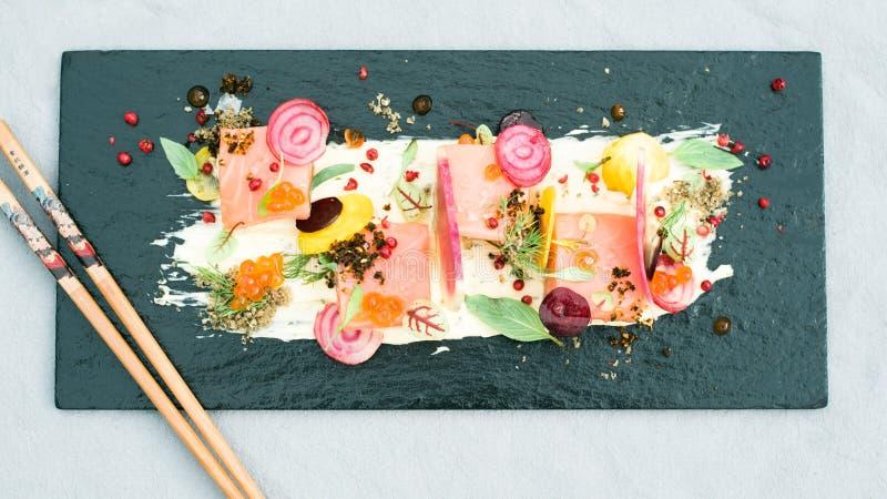Japanese fish dish. Asian fish dish on a black rectangulair plate stock photos