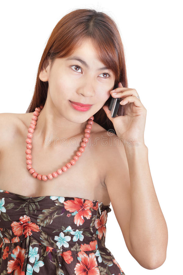Japanese flower girl calling. Japanese-looking Asian girl or young woman in conservative flower dress calling by cellphone and listening with absent gaze stock images