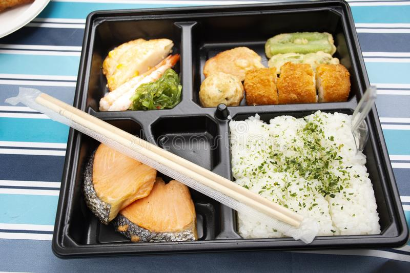 Japanese food bento box rice and fried salmon and vegetables with other cuisine on table stock images