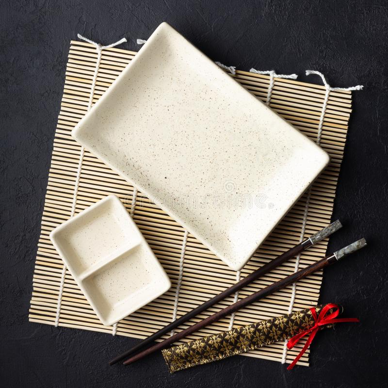 Japanese food concept. Chopsticks and empty sushi plate on bamboo mat. stock photo