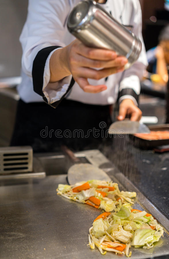 Japanese food: Female chef seasons mixed vegetables on a blazing stock photography