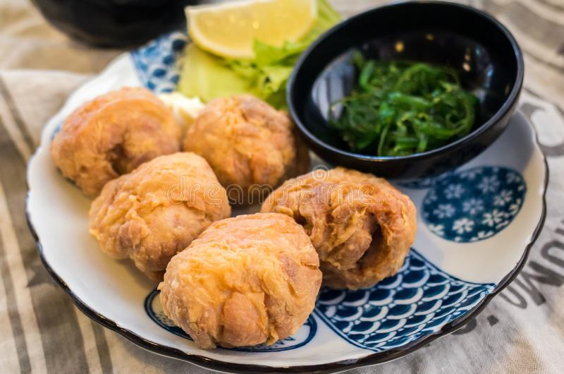 Japanese food: fried chicken karaage with lemon and seaweed salad royalty free stock images