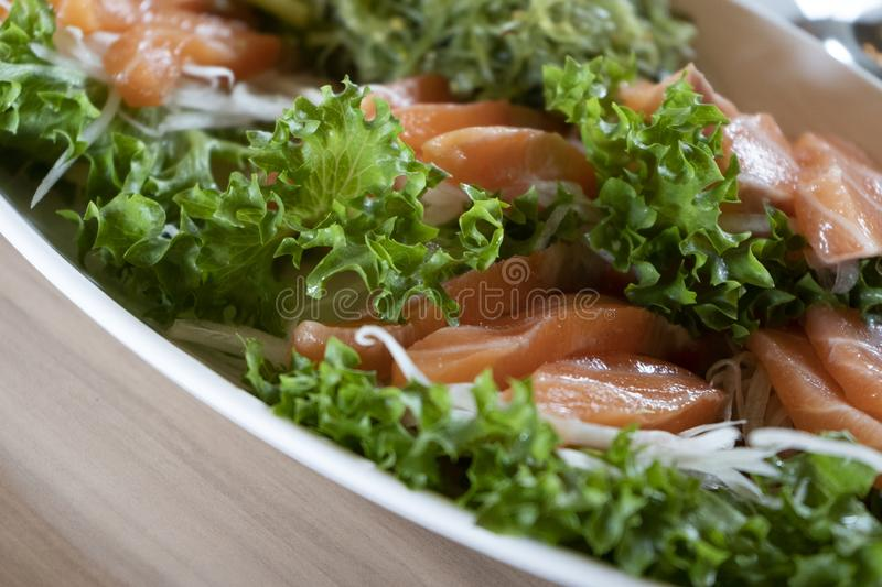 Japanese food, salmon sashimi with Seaweed and vegetables in Ceramic plate on wooden table. stock photography