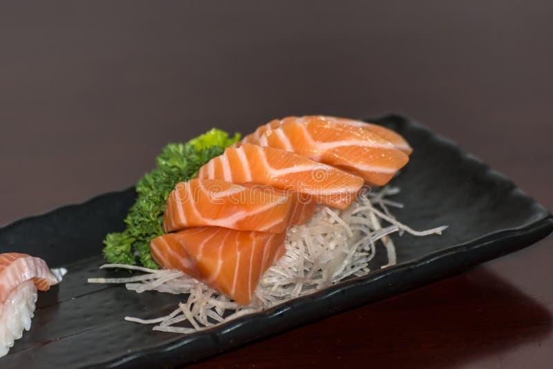 Japanese food sashimi salmon. Japanese food delicacy consisting sashimi salmon of very fresh raw salmon fish sliced into thin pieces serving with radish sliced royalty free stock photography