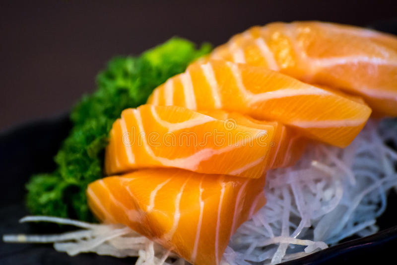 Japanese food sashimi salmon. Japanese food delicacy consisting sashimi salmon of very fresh raw salmon fish sliced into thin pieces serving with radish sliced royalty free stock image