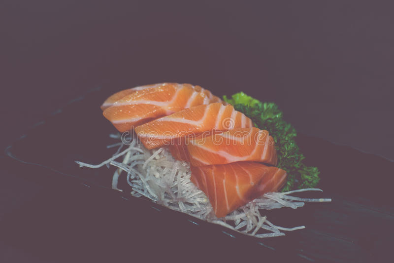 Japanese food sashimi salmon. Japanese food delicacy consisting sashimi salmon of very fresh raw salmon fish sliced into thin pieces serving with radish sliced stock images